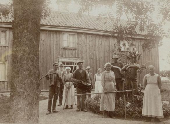 Svartvit gammal bild med kvinnor och män framför trähus.