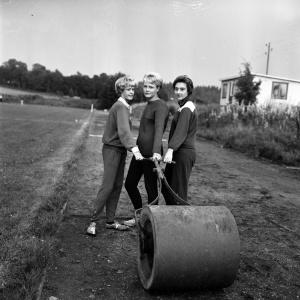 Svartvitt foto föreställande tre unga kvinnor som drar en vält på ett fält. Tidigt 1960-tal.